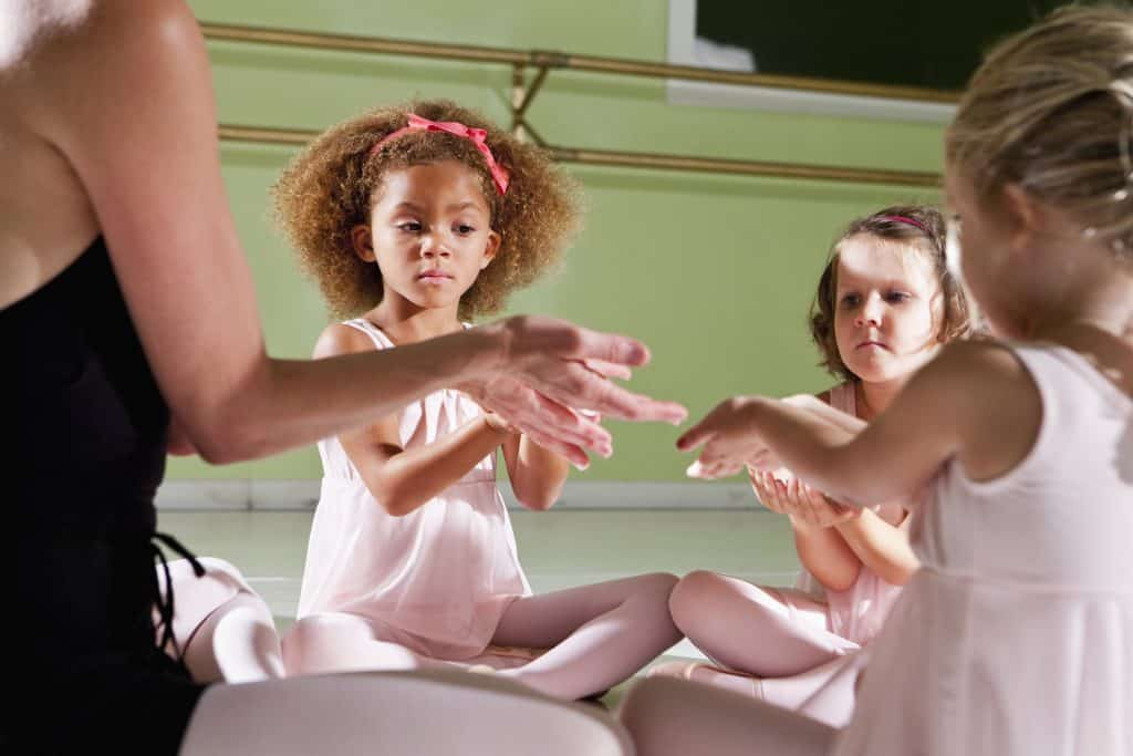 Dance teacher (40s) sitting in circle with little ballerinas (4 years).