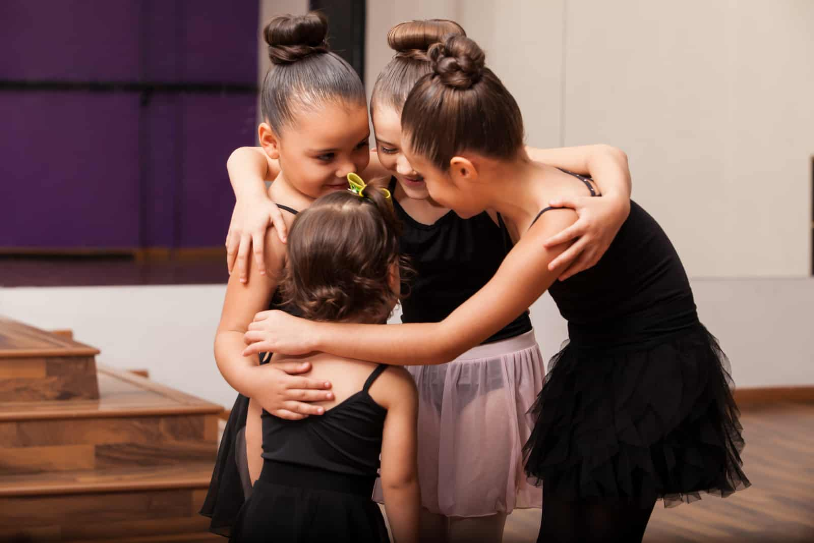 Pretty little Hispanic friends having fun during a ballet class in a dance academy